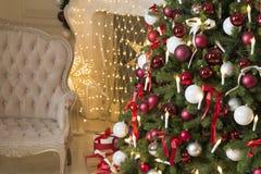 Sala de estar de la Navidad con una chimenea, un sofá, un árbol de navidad y regalos El Año Nuevo hermoso adornó el interior case Imágenes de archivo libres de regalías