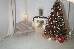 Sala de estar de la Navidad con una chimenea, un sofá, un árbol de navidad y regalos El Año Nuevo hermoso adornó el interior case Foto de archivo libre de regalías