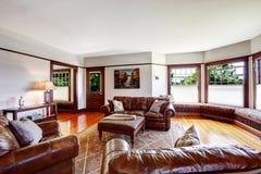Sala de estar lujuriante con el sistema de cuero rico de los muebles Foto de archivo libre de regalías
