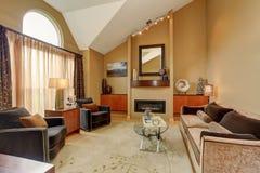 Sala de estar marrón y beige hermosa con el techo saltado imagen de archivo