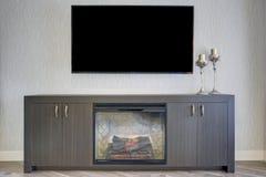 Sala de estar preciosa con el detalle de la TV y de la chimenea fotografía de archivo