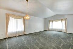 Sala de estar vacía con el techo saltado y la moqueta verde imágenes de archivo libres de regalías
