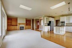 Sala de estar vacía con la cocina conectada, con madera dura imagen de archivo