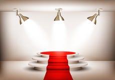 Sala de exposições com o tapete vermelho que conduz a um pódio e a três luzes Imagens de Stock Royalty Free