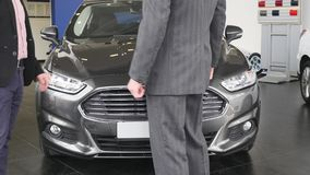 Sala de exposições do carro Negociante do veículo que mostra a homem novo o carro novo Auto negócio, venda do carro, tecnologia e video estoque