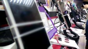 Sala de exposições do dispositivo na loja da eletrônica, compradores que testam e que escolhem smartphones imagens de stock