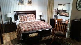 Sala de exposición de los muebles: dormitorio moderno con la mecedora clásica imagenes de archivo