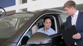 Sala de exposición del coche, distribuidor autorizado del vehículo que muestra a hombre del consumidor el nuevo coche, negocio au almacen de metraje de vídeo