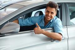 Sala de exposición del coche Hombre feliz dentro del coche de su sueño imágenes de archivo libres de regalías
