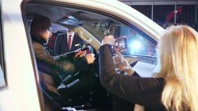 Sala de exposición del coche, mujer que toma las imágenes del hombre que se sientan en salón del nuevo auto en el salón del autom almacen de metraje de vídeo