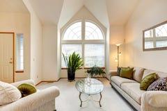 Sala de família luxuosa em tons cremosos macios com teto da altura e a Imagens de Stock Royalty Free