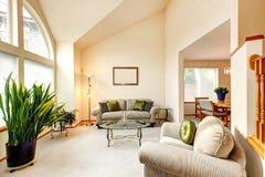 Sala de família luxuosa em tons cremosos macios com teto da altura e a Imagem de Stock Royalty Free
