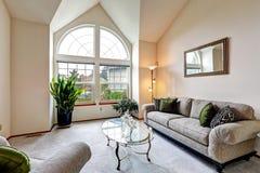 Sala de família luxuosa em tons cremosos macios com teto da altura e a Fotos de Stock