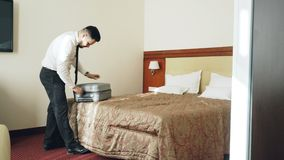 A sala de hotel entrando do homem de negócios que desembala sua mala de viagem pôs sobre o revestimento após o registro Curso, ne video estoque