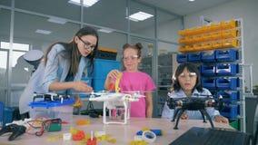 Sala de jogos da engenharia com os adolescentes que trabalham em quadcopters sob a supervisão do ` s do técnico de laboratório video estoque