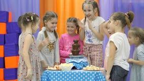 Sala de jogos do ` s das crianças As crianças comem o chocolate de uma fonte do chocolate video estoque