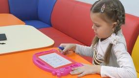 Sala de juegos del ` s de los niños La niña linda pinta en una pluma especial de la pizarra magnética almacen de video