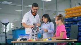 Sala de juegos de la ingeniería con dos adolescencias y un trabajador de sexo masculino que se familiariza con un robot del jugue almacen de video