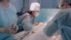 Sala de operaciones durante cirugía Todas las luces encendidas  Los cirujanos que realizan la operación metrajes