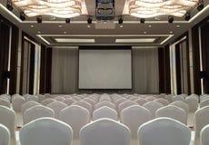 A sala de reunião com luzes do diodo emissor de luz do teto, fileira da conferência de branco preside, com fase e a tela vazia pa imagens de stock