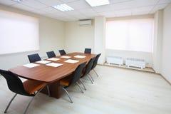 Sala de reunión vacía de la iluminación con la tabla larga Foto de archivo