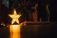 A sala de visitas bonita do Natal com árvore, os presentes e a incandescência decorados ilumina-se na noite foto de stock royalty free
