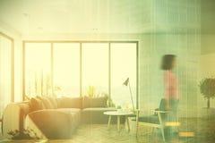 Sala de visitas branca com um sofá cinzento, menina dianteira Fotografia de Stock Royalty Free