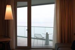 Sala de visitas com a porta de vidro ao balcão Opini?o do mar fotografia de stock royalty free