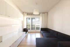 Sala de visitas com sofá escuro e a janela grande foto de stock