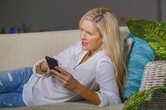 Sala de visitas 40s relaxado adiantada da mulher loura feliz bonita em casa usando meios sociais do Internet no comfor de encontr Fotografia de Stock Royalty Free
