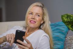 Sala de visitas 40s relaxado adiantada da mulher loura feliz bonita em casa usando meios sociais do Internet no comfor de encontr Fotografia de Stock