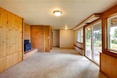 Sala de visitas vazia com as paredes do painel e a chaminé de madeira do ferro fundido Foto de Stock