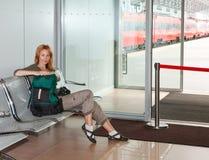 Sala di attesa e treno dietro i portelli trasparenti fotografia stock