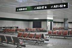 Sala di attesa vuota dell'aeroporto con le indicazioni ai portoni immagini stock