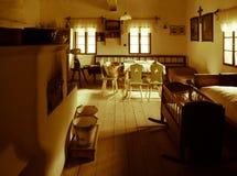 Sala do vintage com cama, berço, fornalha, tabela e cadeiras na casa rural velha Imagem do estilo do Sepia foto de stock royalty free