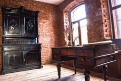 Sala no estilo antigo com uma mesa velha do vestuário velho foto de stock