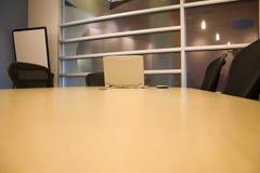 Sala per conferenze con un computer portatile e un PDA sulla tabella Immagine Stock Libera da Diritti