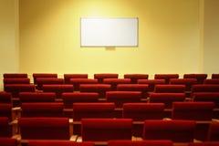 Sala per conferenze vuota con lo schermo. righe delle presidenze Immagine Stock Libera da Diritti