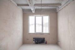 Sala vazia com uma janela e uma bateria em uma casa sob a constru??o, paredes emplastradas, um dircurso no assoalho, multi-n?vel  fotos de stock