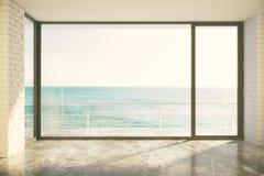 Sala vazia do sótão com a janela grande no assoalho e na vista para o mar Imagem de Stock