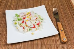 Salad of crab sticks, napa cabbage on dish and fork. Salad of crab sticks with napa cabbage, sweet corn and greens on square white dish and fork on a bamboo royalty free stock image