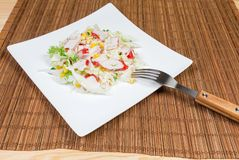 Salad of сrab sticks, napa cabbage on dish with fork. Salad of сrab sticks with napa cabbage, sweet corn and greens on square white dish with fork on a royalty free stock photos