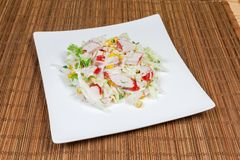 Salad of crab sticks and napa cabbage on dish. Salad of crab sticks with napa cabbage, sweet corn and greens on square white dish on a bamboo table mat royalty free stock photos
