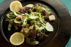 Salad 1. Salad on black plate with lemon slices Stock Photos