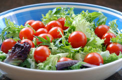 Salad. Undressed cherry tomato and mixed lettuce salad in blue and white bowl, sitting on a granite bench Stock Image