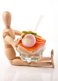 Salad. Wooden mannequin chef holding salad bowl Stock Photography