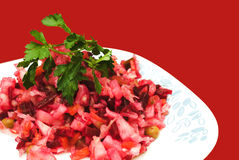 Salad. Vegetable salad on white plate isolated on red background Stock Photo