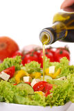 Salad. Pouring olive oil on a fresh salad stock image