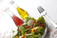 Salad. Fresh colorful salad close up on the table with oil and vinegar Royalty Free Stock Photography
