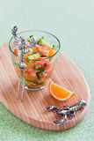 Salad. Crayfish, cucumber and tangerine salad in glass on wooden board, selective focus Royalty Free Stock Image
